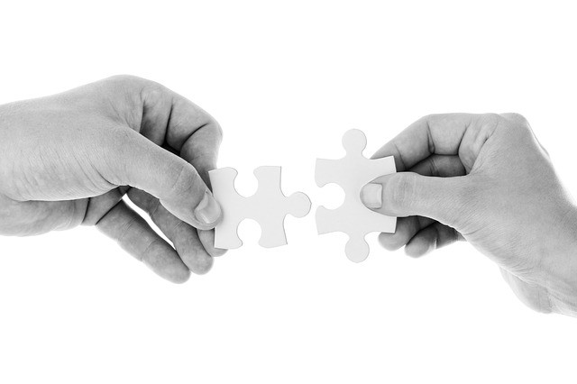 two hands connecting 2 pieces of puzzles in front of a white background