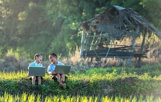 2 children having fun on their laptops in Myanmar