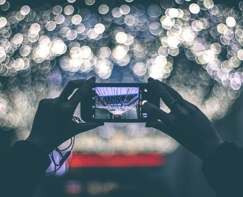 an iphone taking a photo of blurred lights