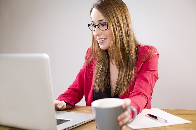 woman trying to drink coffee while working