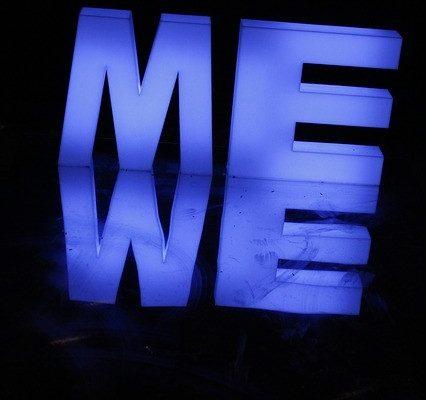 """A purple neon light spelled """"ME"""" glowing in the dark"""