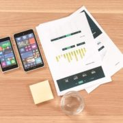 2 smartphones a glass of water and a report showing the results