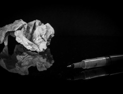 White paper trash and a black pen on a black table