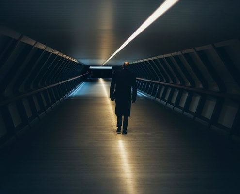 A man walking through a dark tunnel