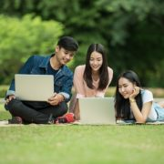 One man and two women having fun with their laptops in a park