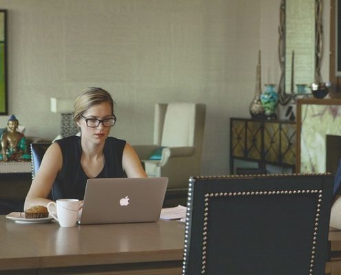 A business woman in a room working on her laptop