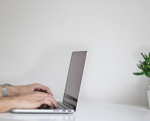 A man typing on a computer in white room next to a plant