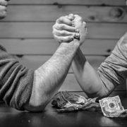 two men betting money on an arm-wrestle match