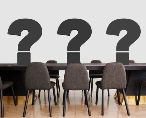 a conference room with a wooden table and wooden chairs with 3 large black question mark icons