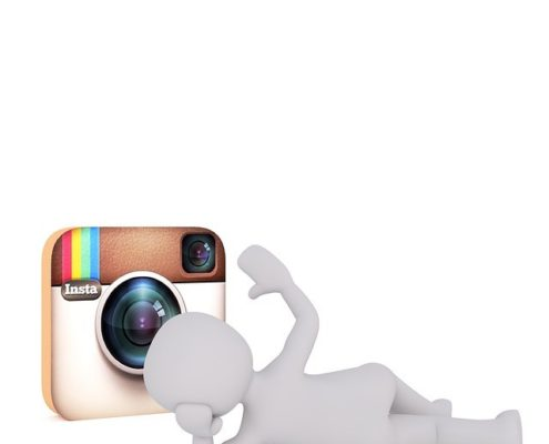 A white doll sleeping in front of the instagram logo