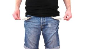 A man wearing jeans and emptying out his pockets