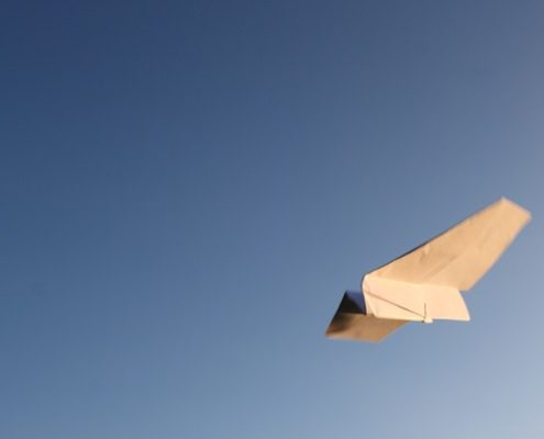 paper airplane flying in a clear blue sky