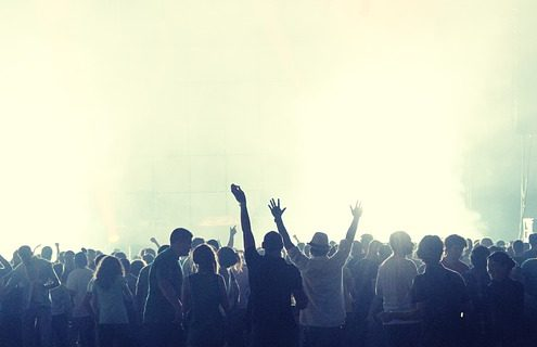 A crowd of people enjoying a music event in a foggy place